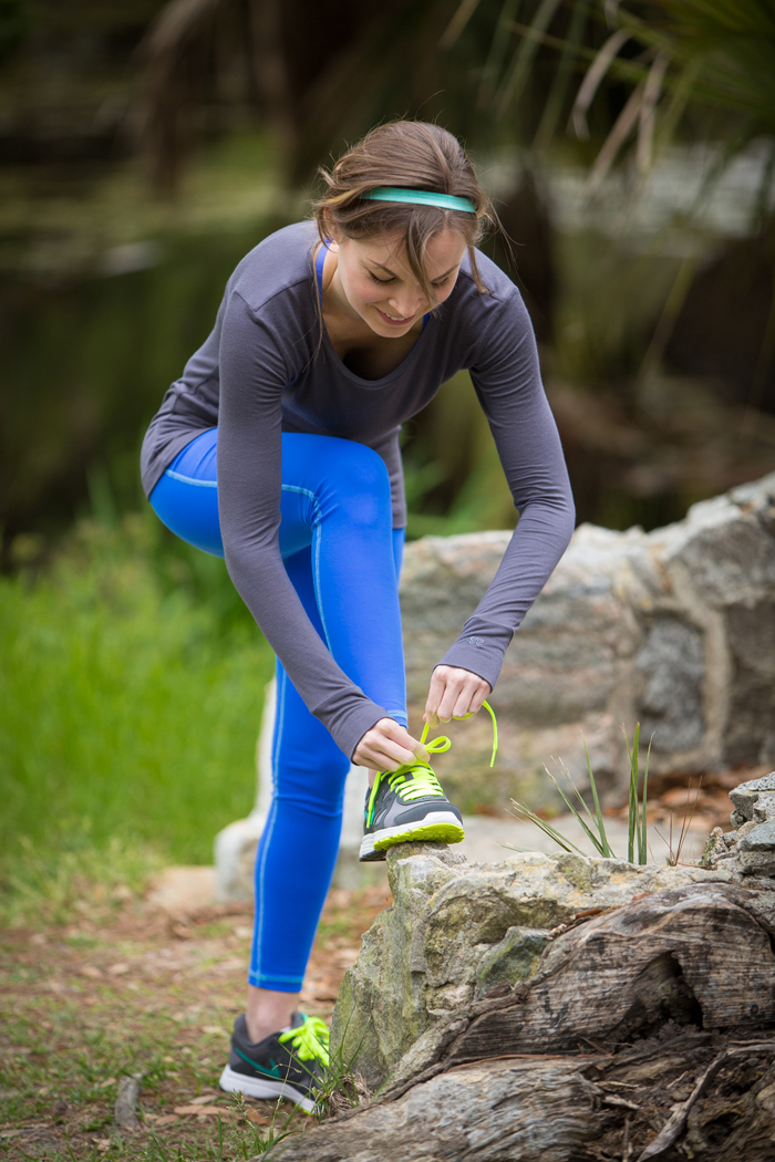 Woman in Blue Leggings Tying Laces for Workout in Park