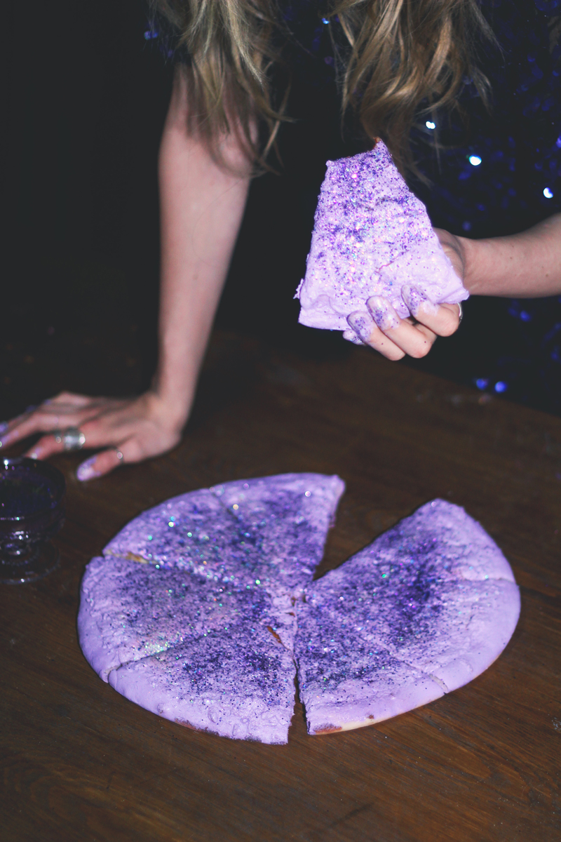 woman eating puple glitter pizza